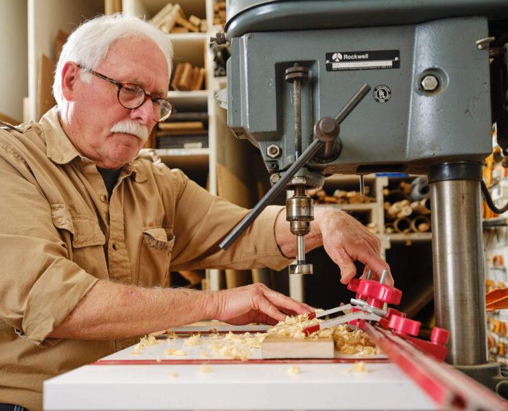 Man using drill press in workshop