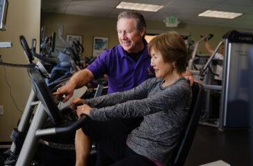 trainer helping woman on bike