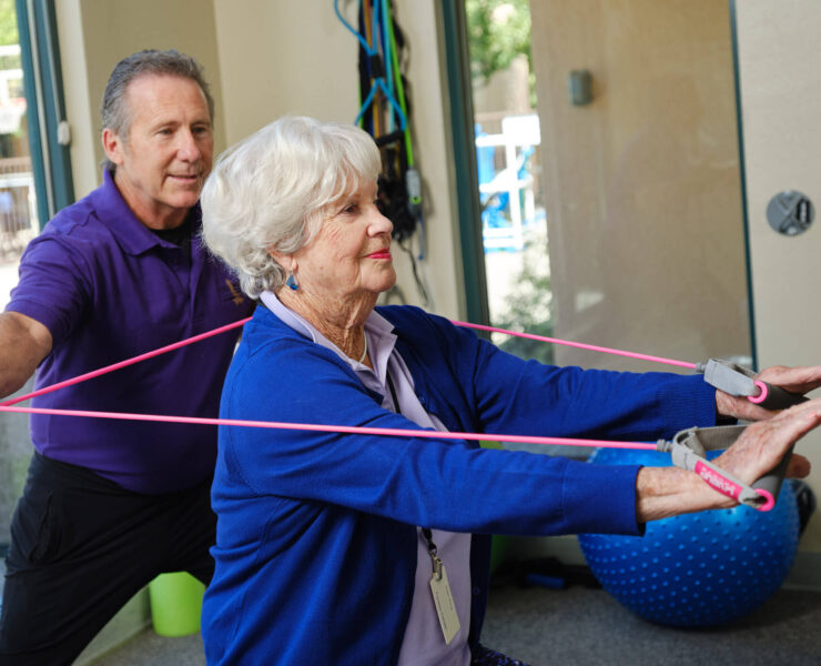 Trainer helping woman exercise