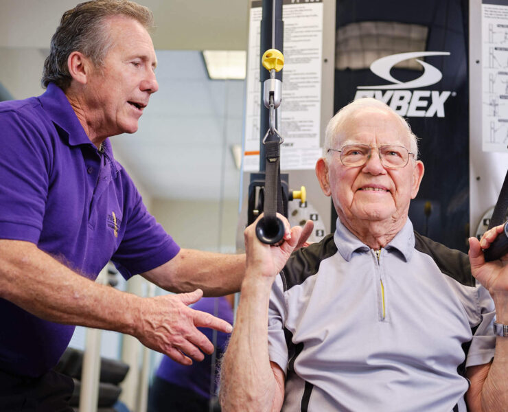 trainer helping man exercise