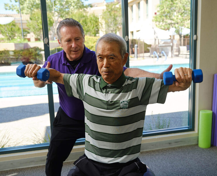 trainer helping resident exercise