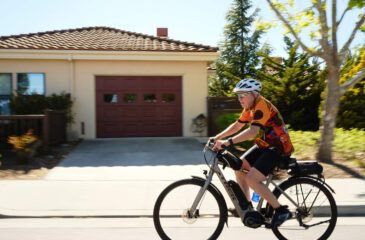 Man bicycling by house with garage